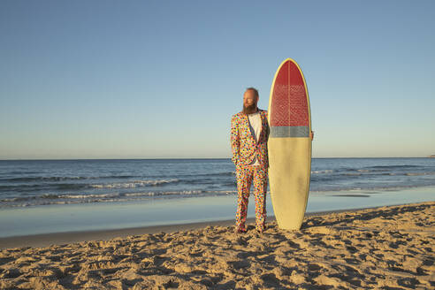 Fashionable man with surfboard looking away while standing against sea - KBF00676