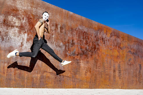 Man wearing white mask talking on mobile phone while running against wall - GGGF00807