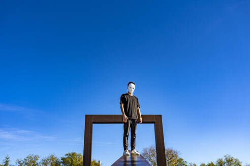 Young man wearing white mask standing on retaining wall against sky - GGGF00810