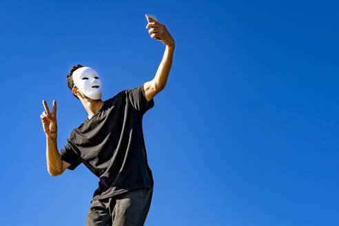 Man wearing white mask taking selfie while standing against clear sky - GGGF00813
