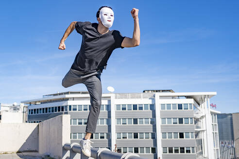Young man wearing white mask running on rooftop during sunny day - GGGF00816