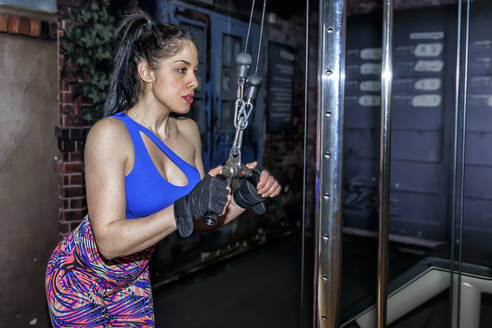 Confident woman pulling exercise equipment in gym - GGGF00828
