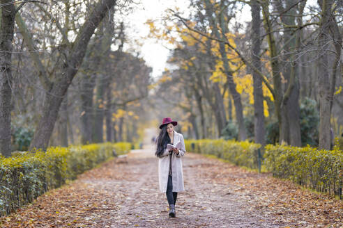 Mid adult woman reading book while walking on land amidst trees in park - GGGF00840