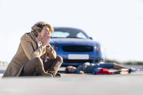 Desperate young man sitting on ground with boy in background lying by car after accident - GGGF00852