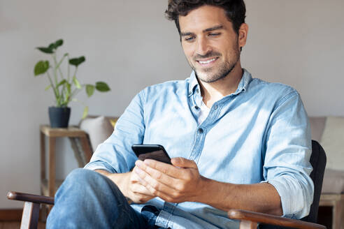 Mid adult man using mobile phone while sitting on armchair at home - SBOF02378