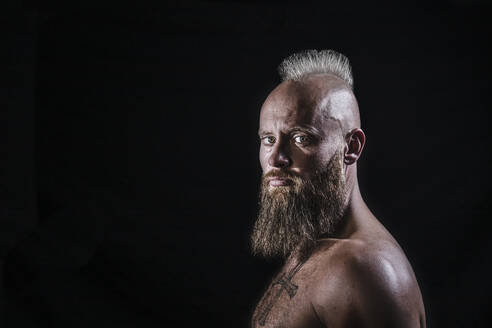 Shirtless male viking with beard and mohawk hairstyle against black background - KBF00688