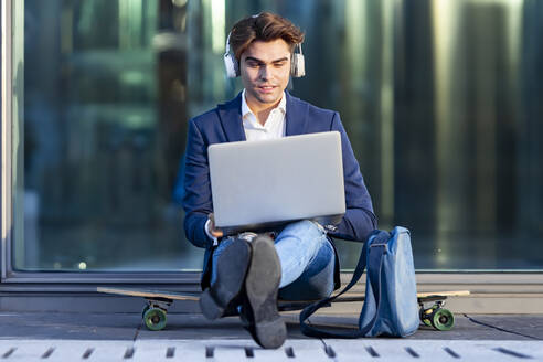 Young businessman working on laptop while listening music sitting on skateboard during sunny day - GGGF00874