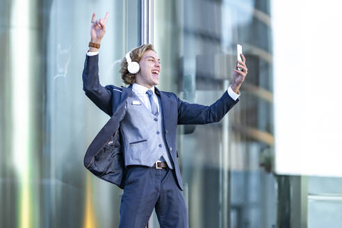 Cheerful young businessman listening music while taking selfie against glass - GGGF00889
