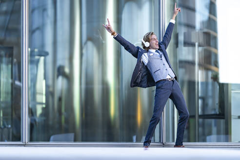 Cheerful young businessman with arms raised dancing while listening music against glass - GGGF00892