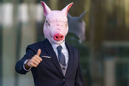 Young businessman wearing pig mask doing thumbs up against office building - GGGF00898
