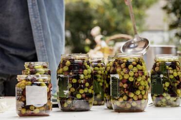 Man preparing olives in jars - AFVF08054