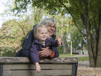 Grandmother and granddaughter leaning on bench while looking away at public park - LAF02637