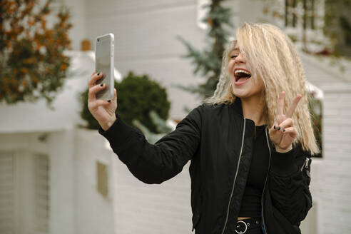 Blond young woman doing peace gesturing while taking selfie through mobile phone - ACPF01052
