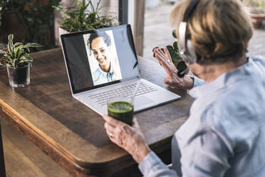 Grandmother waving to granddaughter on video call through laptop while having juice at home - UUF22655