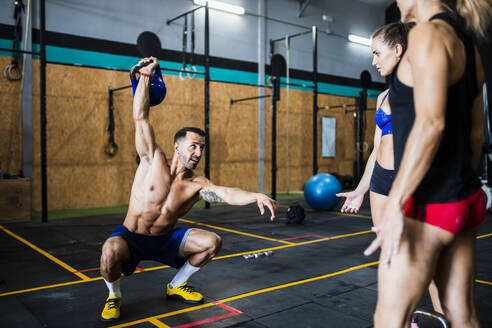 man doing Single arm Kettlebell overhead squat in a crossfit gym while two girls watch him - spain, andalusian, almeria - MIMFF00422