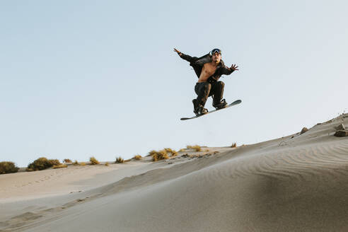 young man snowboarding on sand dunes - spain, andalusia, almeria - MIMFF00437