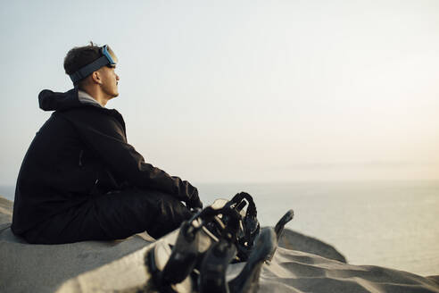 young man sitting on sand dunes next to his snowboard - spain, andalucia, almeria - MIMFF00449