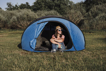Mid adult woman wearing sunglasses and hat relaxing in tent - EBBF02192