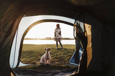 Woman wrapped in shawl camping with dog against lake seen through tent - EBBF02198