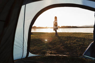 Woman wrapped in shawl standing on grassy land against lake seen through tent - EBBF02201