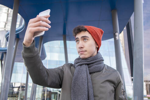 Young man wearing scarf taking selfie against modern building in city - IFRF00314