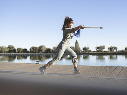Female athlete practicing martial arts with sword by lake against clear sky - JCCMF00901