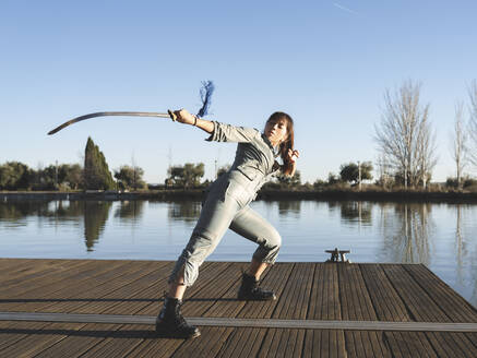 Young woman practicing martial arts with sword against lake at park - JCCMF00910