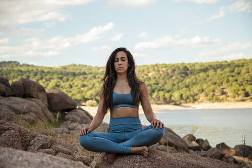 Young woman meditating while sitting cross-legged on rock - MRRF00788
