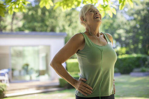 Carefree senior woman with headphones exercising in summer garden - CAIF30086