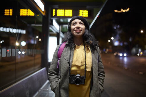 Woman standing with a camera waiting at the bus station at night - CAVF91793