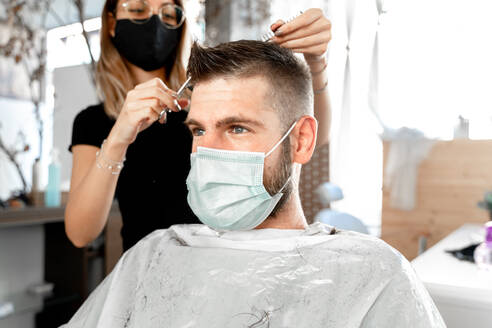 Female master with scissors cutting hair of male customer in protective mask during grooming procedure in salon at coronavirus pandemic time - ADSF20111