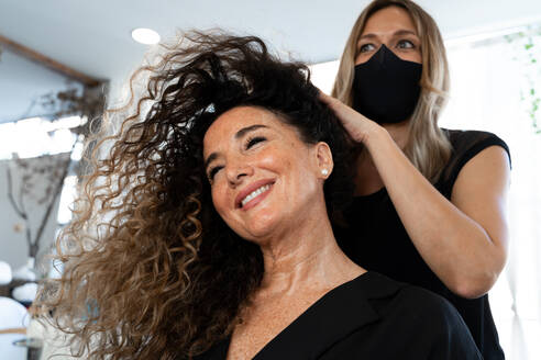 Professional hairdresser in black protective mask using curling tongs while making hairdo to long haired female customer in salon - ADSF20117