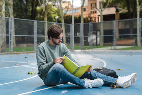 Young man studying while reading book at basketball court in university - JMPF00783