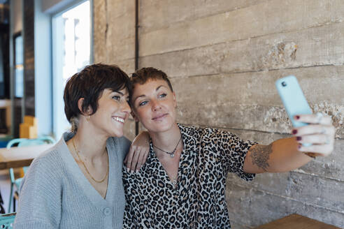 Friends taking selfie on mobile phone while sitting at restaurant - JRVF00105
