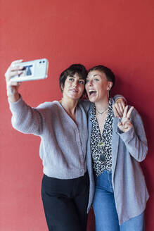 Young woman taking selfie on mobile phone with excited friend while standing against red wall - JRVF00129
