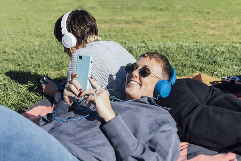 Smiling woman wearing headphones using mobile phone while leaning on friend lying at park - JRVF00147