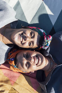 Happy friends wearing headscarf smiling while resting on blanket - JRVF00162