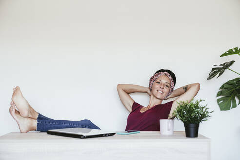 Smiling businesswoman relaxing with hands behind head against white wall at home office - EBBF02219