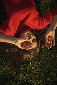 Happy girl wearing red laying on grass, Amsterdam, The Netherlands - AXHF00098