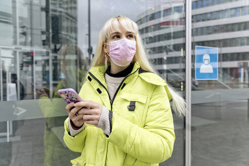 Young woman wearing face mask using smart phone while standing against glass wall - FLLF00572