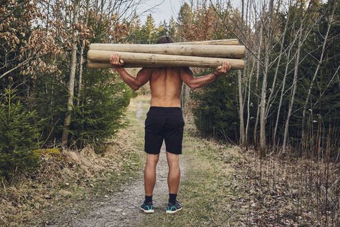 Shirtless male athlete carrying logs in forest - KDF00741