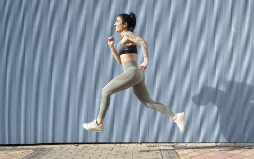 Mid adult woman running on footpath by blue wall - DAMF00653