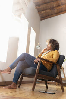 Thoughtful woman with hand on chin looking away while sitting on armchair at home - SBOF02525