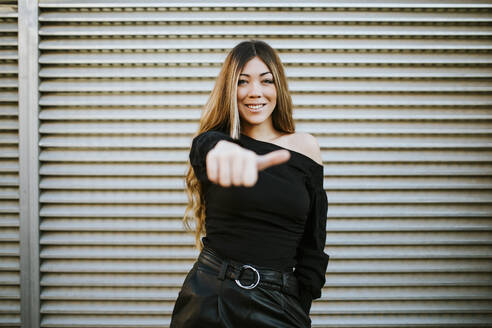 Smiling young woman showing thumbs up while standing against wall - MIMFF00465