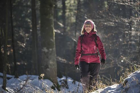 Woman walking in forest in Winter - MRF02451