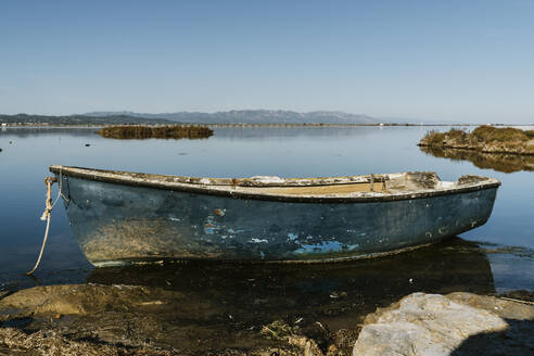 Abandoned rowboat moored in lake against clear sky on sunny day at natural park, Ebro Delta, Spain - AFVF08071