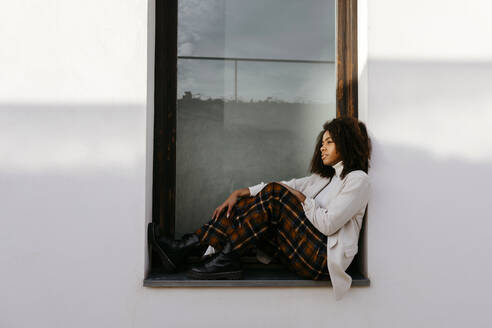 Thoughtful woman with afro hair sitting on window sill of building - TCEF01447