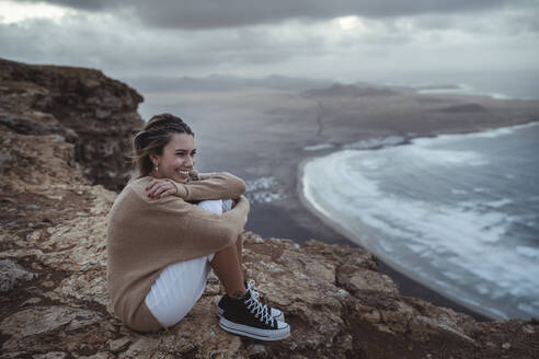Young tourist girl visiting the Famara viewpoint in lanzarore, spain - SNF01024