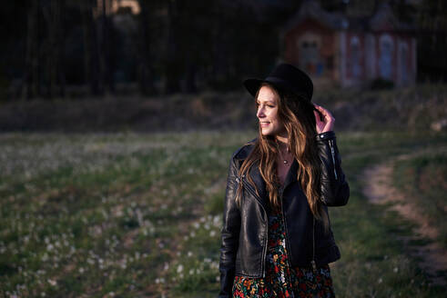 Stylish female wearing hat and black leather jacket standing in field at sunset and looking away - ADSF20205