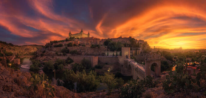 View across river of old city Toledo in Spain with medieval castles and fortresses at sunset time with cloudy sky and reflection in river water - ADSF20271